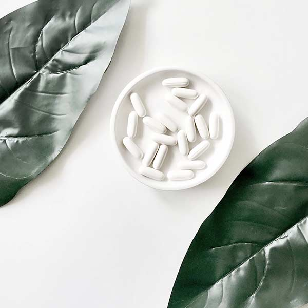 PIlls in a dish, surrounded by leaves
